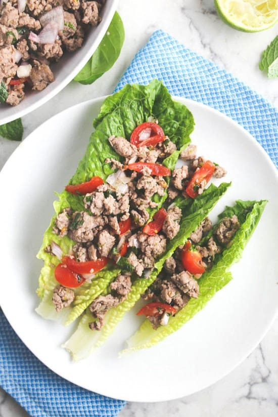 Thai larb gai (ground chicken salad) served on romaine lettuce with tomatoes