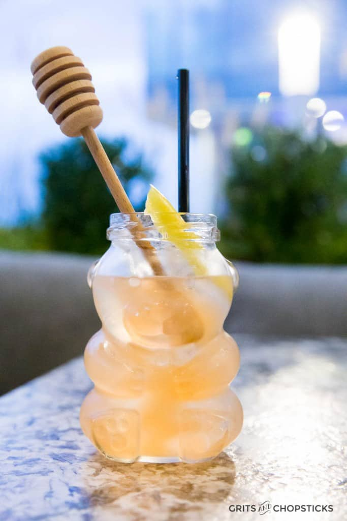 The Bee's Knees Cocktail at Earl's Kitchen + Bar is served in a honey bear jar with a honeycomb stirrer -- a cheeky yet sophisticated twist on a classic gin cocktail